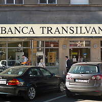 TIMISOARA, ROMANIA - APRIL 21:  People walk in front of a branch of Banca Transilvania on April 21, 2013 in Timisoara, Romania.  Romania has abandoned a target deadline of 2015 to switch to the single European currency and will now submit to the European Commission a programme on progress towards the adoption of the Euro, which for the first time will not have a target date. (Photo by Marco Secchi/Getty Images)