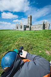 Photographer in front of Ross Errilly Friary, County Galway, Ireland
