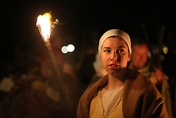 © Licensed to London News Pictures. 20/02/2016. York, UK. A woman's face is lit by a burning torch during the finale of the annual Jorvik Viking Festival in York, North Yorkshire. The historic city was transformed into a fiery battleground as this year's end to the week long festival told the story of the infamous Battle of Assundun. The festival, which is run by the Jorvik Viking Centre, takes place every February in tradition of an ancient Viking festival known as Jolablot.  Photo credit : Ian Hinchliffe/LNP
