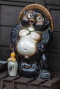 """Honored in a stylized statue, this tanuki, or Japanese raccoon dog (Nyctereutes procyonoides viverrinus) is a subspecies of Asian raccoon dog, in the canid family. In Japanese folklore, the legendary tanuki is reputed to be mischievous and jolly, a master of disguise and shapeshifting, but somewhat gullible and absentminded. The tanuki is a common theme in Japanese art and statuary. """"Tanuki"""" is often mistakenly translated into English as """"badger"""" or """"raccoon"""" (as used in the US version of the movie Pom Poko and outlined in Tom Robbins' book Villa Incognito), two unrelated types of animals with superficially similar appearances.  The city of Takayama (""""tall mountain"""") lies in the heart of the Japan Alps, in the Hida region of Gifu Prefecture. Commonly differentiated as Hida-Takayama, city has the largest geographic area of any municipality in Japan."""
