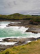 A storm descends onto Curio Bay, Catlins, New Zealand, kicking up large waves.