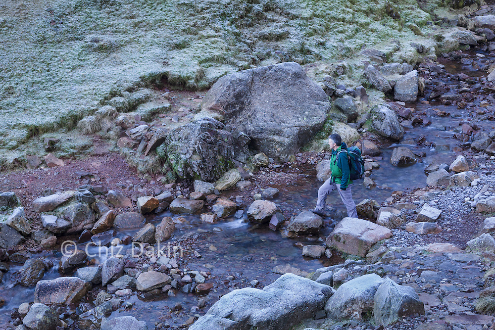 Walker crossing stepping stones across Ruddy Gill, on the descent from Sprinkling Tarn/Great Gable/Scafell Pike
