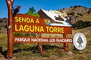 Red headed woodpecker and route sign to Laguna Torre under Cerro Torre peak, Parque Nacional Los Glaciares, Patagonia, Argentina.