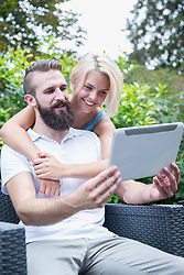 Happy young couple taking a selfie with digital tablet in garden, Bavaria, Germany
