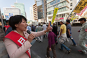 A politician from the Japanese Communist Party waves to people marching for workers' rights and to protest against some of Prime Minister Shinzo Abe's policies during the May Day Rally in Tokyo, Japan. Friday May1st 2015