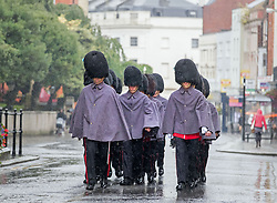 Guards march up to Windsor Castle in the rain as a yellow weather warning for rain has been issued for parts of the UK.