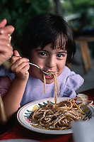November 1989, Ischia, Italy --- Girl Eating Bucatini --- Image by © Owen Franken/CORBIS