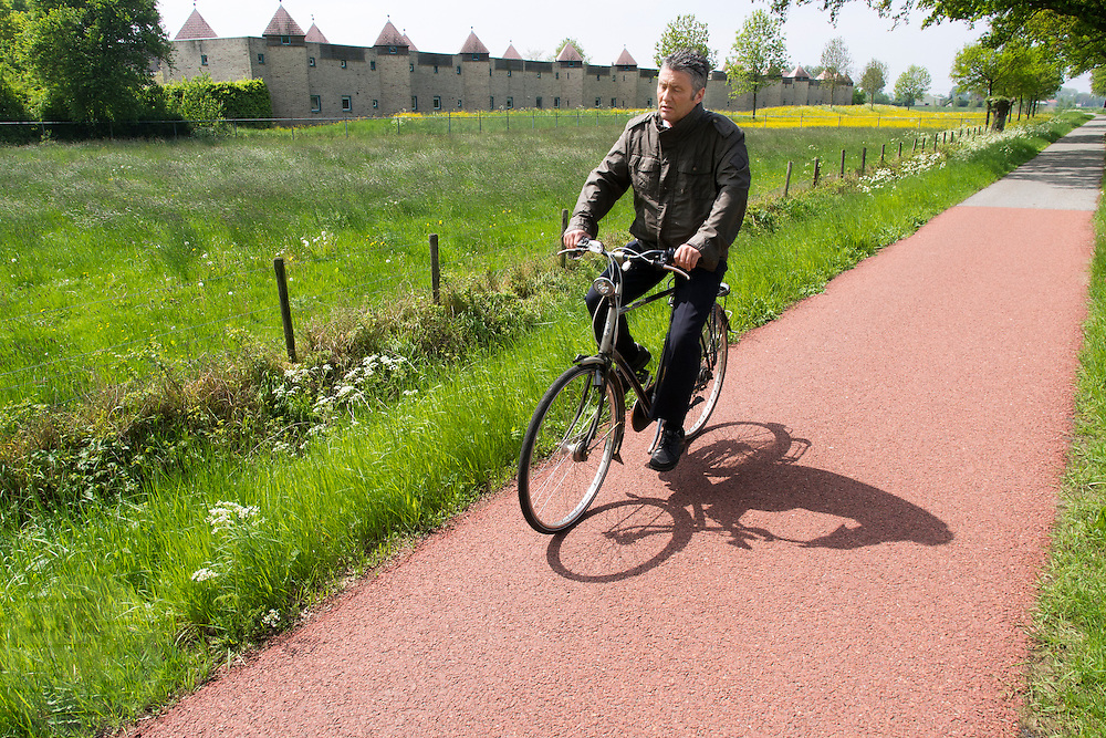 Een man fietst voorbij de zogenaamde kasteelwoningen aan de rand van Zevenaar, een plaatsje in de streek De Liemers in het oosten van Nederland. De woningen zijn zo ontworpen dat ze gelijk een geluidswal zijn voor de achterliggende wijk.<br /> <br /> A man cycles past the so-called castle houses on the edge of Zevenaar, a town in the region the Liemers in the east of the Netherlands. The houses are designed to be like a sound barrier for the underlying district.