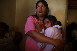 A young girl is comforted by her aunt during the wake of the girl's mother in the state of Chihuahua, near Ciudad Juarez.  The mother was a factory work and was killed during a shooting on the bus that was taking her home.