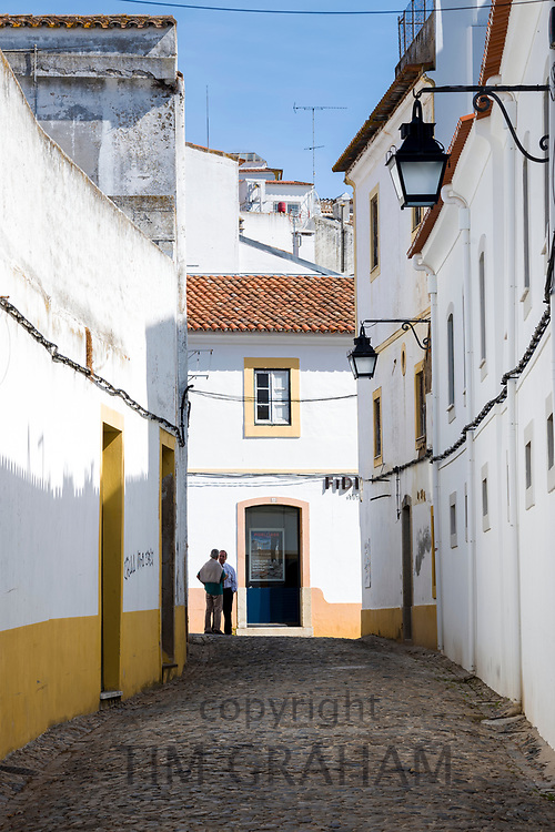 People in typical street scene of white and yellow houses, lanterns and narrow cobble street in Evora, Portugal