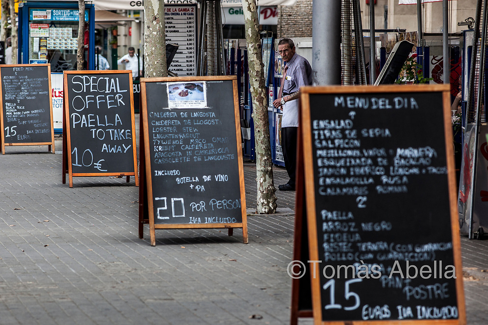 In the main thoroughfare of the La Barceloneta neighbourhood, the Passeig de Joan de Borbó promenade, restaurant signs occupy most of the sidewalk: public space is privatised in benefit of the tourist sector.
