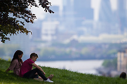A couple rest in the shade as the hazy sunshine partially obscures the City skyline in London, seen from Maze Hill, Greenwich as Mayor Sadiq Khan announces air toxicity alerts for the Capital. London, May 08 2018.