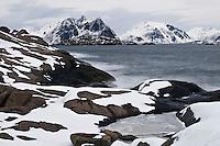Rocky snow covered shoreline near Stamsund, Vestvågøy, Lofoten Islands, Norway