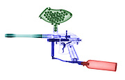 X-Ray of a Paintball Gun. A paintball gun is a gun that shoots round balls of paint using high pressure carbon dioxide gas.  The gas cylinder is shown in the picture, as are the paint balls.  Paintball is now a sport.