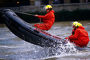 Leaping over waves, London Fire Brigade (LFB) fire fighters train on the River Thames using an inflatable dinghy. Crossing the wake of another vessel, the inflatable jumps, as the fire-fighter holds on tight to a rope at the boat's bow while two colleagues sit on the read for ultimate balance so the dinghy can ride over the turbulent waters. Spray from the waves splash them although they wear waterproofs and fire service helmets.