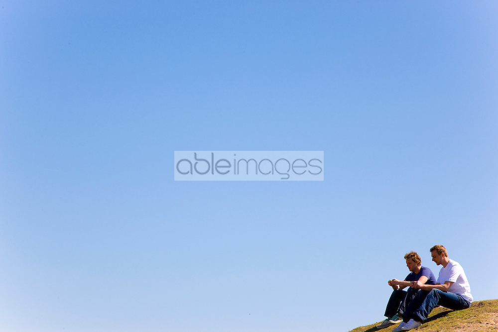 Portrait of two young men sitting on top of hill talking