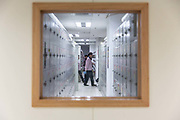 An employees stands in front of rows of lockers at a Pegatron Corp. factory in Shanghai, China, on Friday, April 15, 2016. This is the realm in which the worlds most profitable smartphones are made, part of Apple Inc.s closely guarded supply chain.