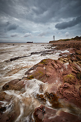 A container ship passes the lighthouse at Black Nore on the rocky coast of the Bristol Channel.
