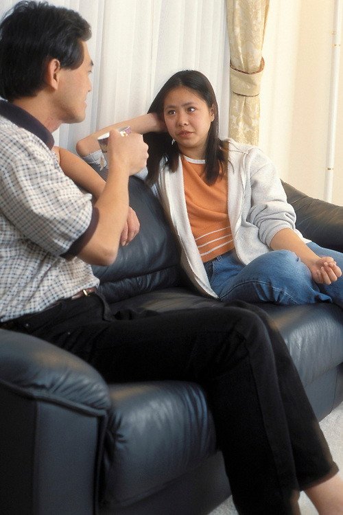 Asian-American father drinking coffee and talking with teenage daughter on couch.  Model Release.<br /> ©Bob Daemmrich