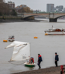 © Licensed to London News Pictures. 15/02/2020. London, UK. Pictured, the dingy is towed back to the shore. A dingy capsizes on the river Thames at Putney during Storm Dennis. The sailor scrambles for the safety of the hull before righting it. Unfortunately it seems to have broken its mast as Storm Dennis hits London and the South East with high winds and heavy rain forecast for the weekend. Photo credit: Alex Lentati/LNP