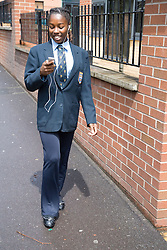 Teenaged girl walking to school listening to music on her MP3 player,
