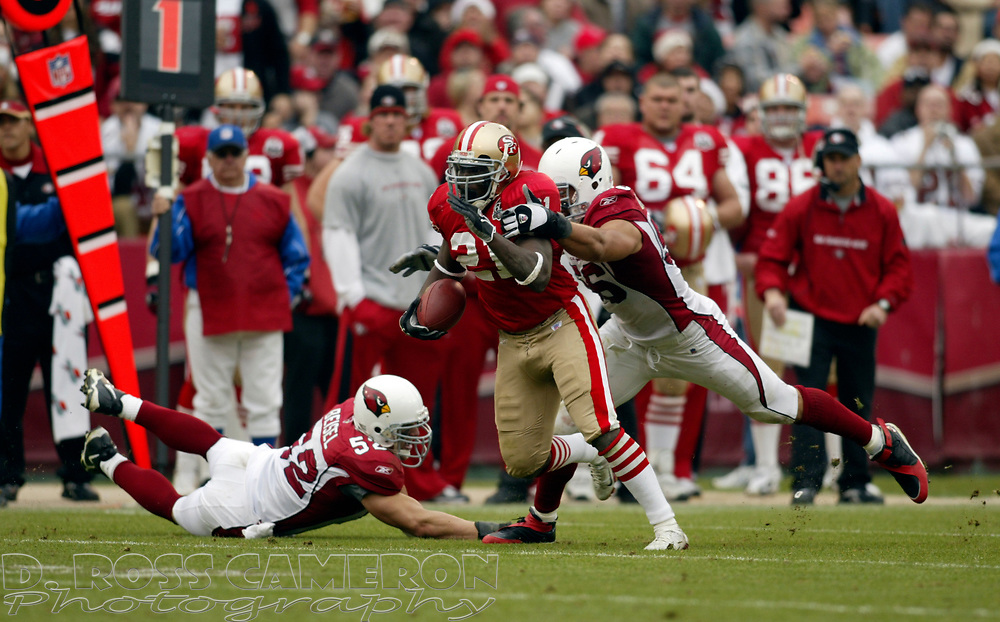 San Francisco 49ers running back Frank Gore (21) bolts between Arizona Cardinals defenders Monty Beisel (52) and Chike Okeafor (56) during the second quarter of an NFL football game, Sunday, Dec. 24, 2006 at Candlestick Park in San Francisco. The Cardinals won, 26-20. (D. Ross Cameron/The Oakland Tribune)