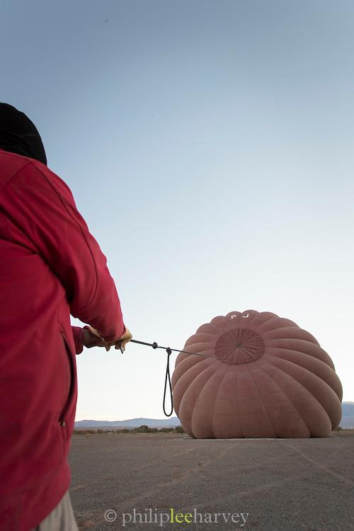 Man preparing hot air balloon to start his adventure, Atacama Desert, Chile