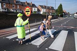Mother walking children to school crossing a zebra crossing,