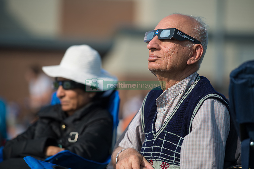 People are seen as they watch a total solar eclipse through protective glasses in Madras, Oregon on Monday, Aug. 21, 2017. A total solar eclipse swept across a narrow portion of the contiguous United States from Lincoln Beach, Oregon to Charleston, South Carolina. A partial solar eclipse was visible across the entire North American continent along with parts of South America, Africa, and Europe.  Photo Credit: (NASA/Aubrey Gemignani)