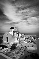 Black and white photo of a church with bells in Santorini, Greece.