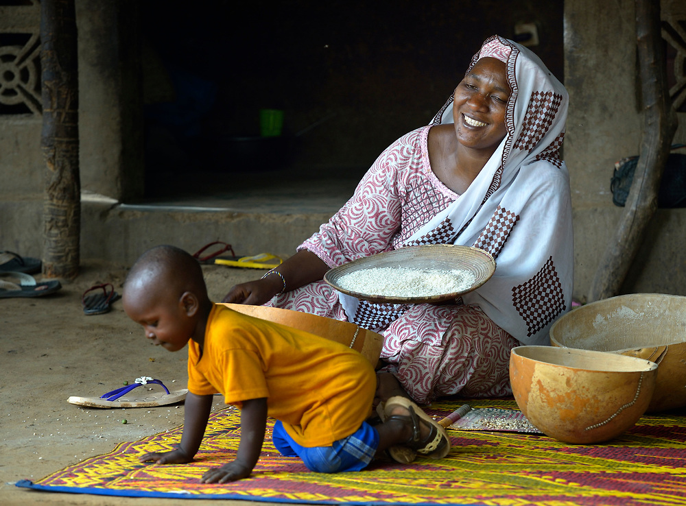 Aramatou Maiga laughs at one of her children as she winnows grain to cook for her family in Segou, Mali. She was displaced when Islamist rebels seized the north of the country, including her home town of Gao, in 2012. The Islamists were chased out in early 2013 by French troops. Many displaced and refugee families have yet to return, preferring to wait for better security and improved economic conditions in the north.
