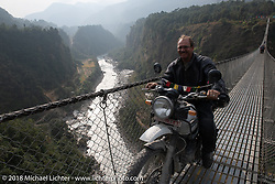 Kiwi Mike Tomas on the Kusma Gyadi Bridge, the tallest (443') and one of the longest (1,128') suspension bridges in the country, on Day-7 of our Himalayan Heroes adventure riding from Tatopani to Pokhara, Nepal. Monday, November 12, 2018. Photography ©2018 Michael Lichter.
