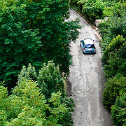 A car driving through a forested area in the town of Tarcento, Italy.