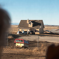 Phoebe Morgan looks out her back door to her neighbor Jason Joe's home in the Tse'ii'ahi' Navajo Housing Authority Subdivision in Standing Rock, New Mexico Thursday. Joe has had many roof issues including water leaks caused by missing shingles and Joe has patched multiple areas on the roof himself which can be seen from Morgan's home.