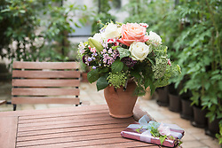 Gift with bouquet of flowers on table in garden, Munich, Bavaria, Germany
