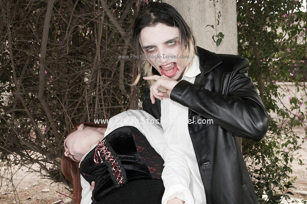 a couple in their 20s dressed up as Vampires Model release available