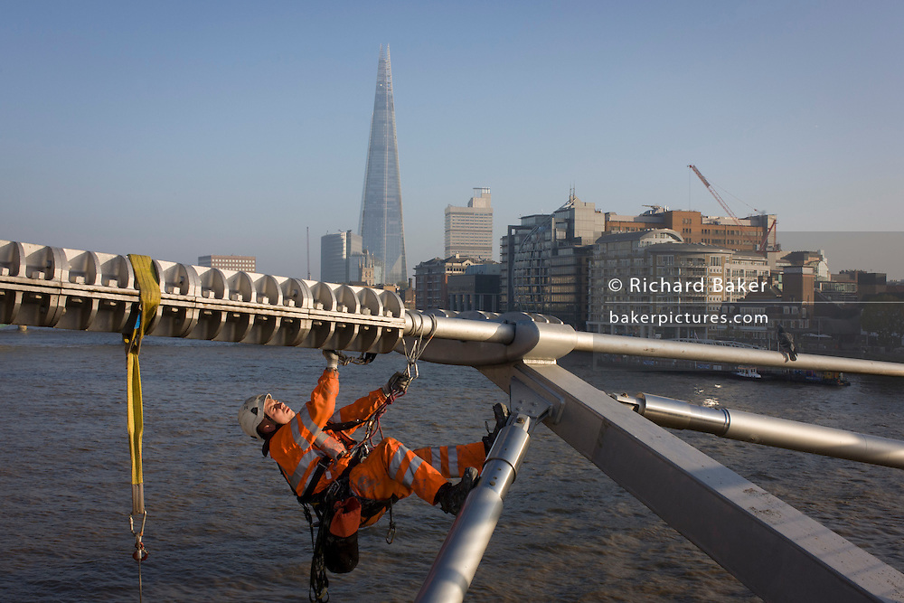 With the Shard in the background, a cleaning crew with the contractor conway wash down surfaces on the Millennium Bridge for the first time in its 15 year history. A cleaning crew with the contractor Conway wash down surfaces on the Millennium Bridge for the first time in its 15 year history.