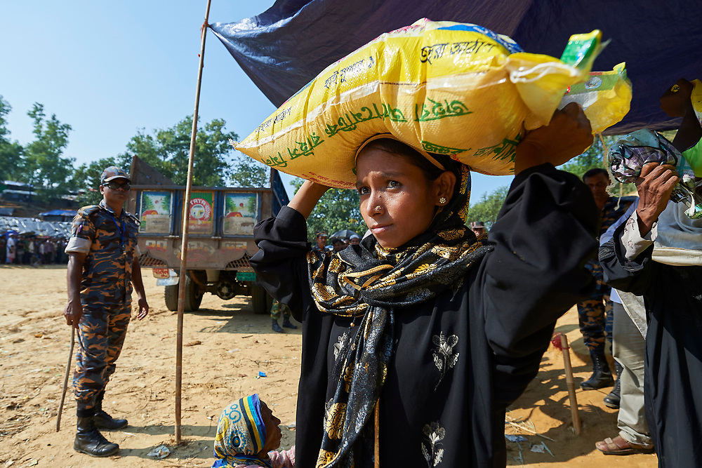 A Rohingya woman in the Balukhali Refugee Camp near Cox's Bazar, Bangladesh, carries a bag of rice she received from the Bangladesh government. <br /> <br /> More than 600,000 Rohingya have fled government-sanctioned violence in Myanmar for safety in Bangladesh.