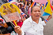 05 MAY 2010 - BANGKOK, THAILAND: A woman holds up photos of the Thai King and Queen while she waits for the King's motorcade in front of the palace in Bangkok, Wednesday, May 5. Wednesday was Coronation Day in Thailand, marking the 60th anniversary of the coronation of Thai King Bhumibol Adulyade, also known as Rama IX. He is the world's longest serving current head of state and the longest reigning monarch in Thai history. He has reigned since June 9, 1946 and his coronation was on May 5, 1950, after he finished his studies. The King is revered by the Thai people. Thousands lined the streets around the Grand Palace hoping to catch a glimpse of the King as his motorcade pulled into the palace. The King has been hospitalized since September 2009, making only infrequent trips out of the hospital for official functions, like today's ceremonies.   PHOTO BY JACK KURTZ