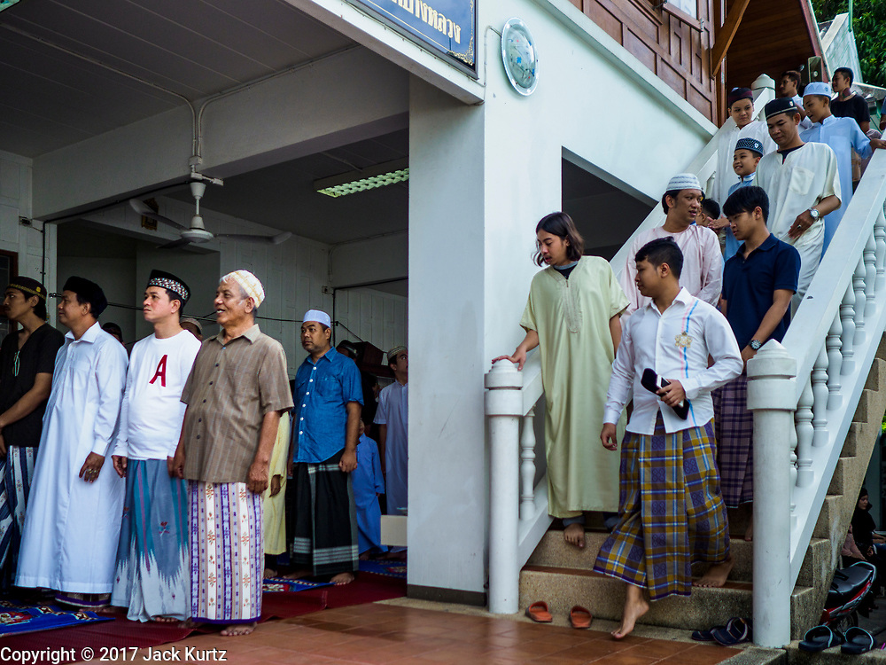 25 JUNE 2017 - BANGKOK, THAILAND: Men arrive at Bang Luang Mosque for Eid al-Fitr prayers. Eid al-Fitr is also called Feast of Breaking the Fast, the Sugar Feast, Bayram (Bajram), the Sweet Festival or Hari Raya Puasa and the Lesser Eid. It is an important Muslim religious holiday that marks the end of Ramadan, the Islamic holy month of fasting. Muslims are not allowed to fast on Eid. The holiday celebrates the conclusion of the 29 or 30 days of dawn-to-sunset fasting Muslims do during the month of Ramadan. Islam is the second largest religion in Thailand. Government sources say about 5% of Thais are Muslim, many in the Muslim community say the number is closer to 10%.    PHOTO BY JACK KURTZ