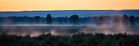 Early morning mist rises off from the Henry's Fork River in Idaho as the glow of sunrise illuminates the sky.