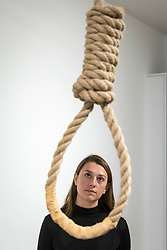 "© Licensed to London News Pictures. 13/11/2018. LONDON, UK. A staff member views a hangman's noose.  Preview of ""Glad I Did It"", a new work by Irish artist Christina Reihill at Bermondsey Project Space.  The interactive artwork looks at the life and death of Ruth Ellis, the last woman to be hanged in Britain, after she shot her lover, racing driver, David Blakely in 1955.  On display are the artist's interpretation of Ruth Ellis' prison cell, including furniture and props, the hanging room together with a video display of the artist in conversation.   The show runs 14 November to 1 December 2018.  Photo credit: Stephen Chung/LNP"