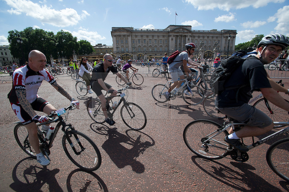 © London News Pictures. 03/08/2013. London, UK. Cyclists pass in front of Buckingham Palace as  Cycling enthusiasts of all ages take part in the Prudential RideLondon cycling event through central London. RideLondon is an annual two-day festival of cycling, part of the legacy of the 2012 Games. Photo credit: Ben Cawthra/LNP