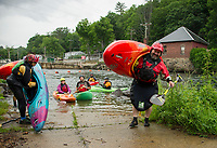 """Jeff Magee of Enfield, CT hauls out his kayak ready for another run down the Winni River during Mill City Park's """"Winni River Days"""" whitewater festival in Franklin on Saturday.  (Karen Bobotas/for the Laconia Daily Sun)"""
