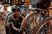 Modi street's best bicycle mechanic, Akram, pull 7:30 am to 10 pm days repairing a steady stream of utility bikes. Akram fixes an average of 25 flats per day and his father's 3-man shop rebuilds/repairs 40 wheels per day in total - Bombay/Mumbai - India
