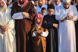 June 15, 2018 - Khan Younis, Gaza Strip - Palestinian Muslim worshipers perform Eid al-Fitr prayer, at the Israel-Gaza border in Khan Younis in the southern Gaza Strip on June 15, 2018. Eid al-Fitr marks the end of Muslim's holy fasting month of Ramadan when faithfuls abstain from eating, drinking, smoking and sexual activities from dawn to dusk  (Credit Image: © Ashraf Amra/APA Images via ZUMA Wire)