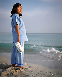 Rosalie Villanueva, 35, stands on a beach in Abu Dhabi, United Arab Emirates on Feb. 2007.  Rosalie, who works at the Al Rahba Hospital as a nurse, met her husband Christopher Villanueva  while they were both OFWs working overseas. They both later got jobs in Abu Dhabi, but decided to leave one of their three children, Precious Lara, with Rosalie's parents in the Philippines. Isolation and damaged family relations due to time spent apart is one of the major sacrifices made by OFWs.