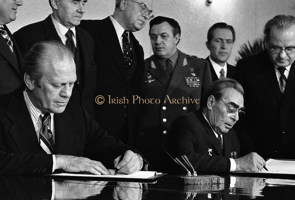 President Gerald Ford and Soviet General Secretary Leonid Brezhnev sign a Joint Communiqué following talks on the limitation of strategic offensive arms. The document was signed in the conference hall of the Okeansky Sanitarium, Vladivostok, USSR.  1974