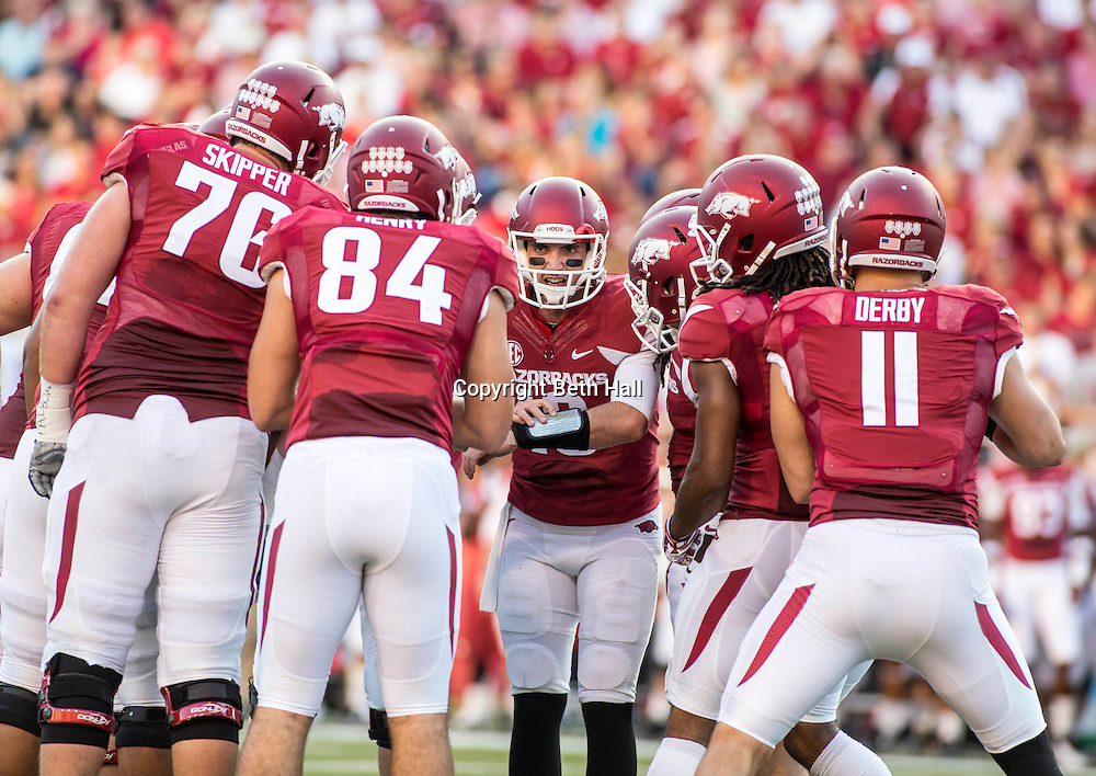 Sep 20, 2014; Fayetteville, AR, USA; Arkansas Razorbacks quarterback Brandon Allen (10, center) calls a play as offensive tackle Dan Skipper (74) tight end Henry Hunter (84) tightened A.J. Derby (11) and other players look on during the first half of a game against Northern Illinois University Huskies at Donald W. Reynolds Razorback Stadium. Mandatory Credit: Beth Hall-USA TODAY Sports