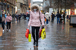 Glasgow, Scotland, UK. 20 November 2020. On the day when the severest level 4 lockdown will be imposed at 6pm, shoppers are out on the streets of Glasgow doing last minute Christmas shopping before the shops close for 3 weeks. Pictured;  woman walks along on Buchanan Street. Iain Masterton/Alamy Live News